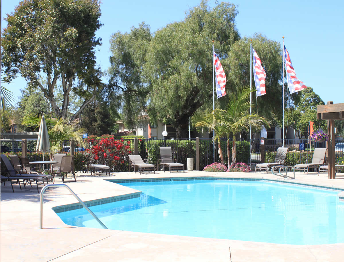 fenced pool and patio in apartment complex with lounge chairs, table with umbrella, and shade awning