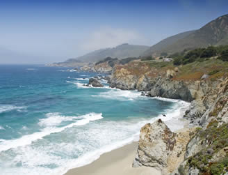 empty sandy beach with rocky cliffs and big waves that is part of the central california coastline