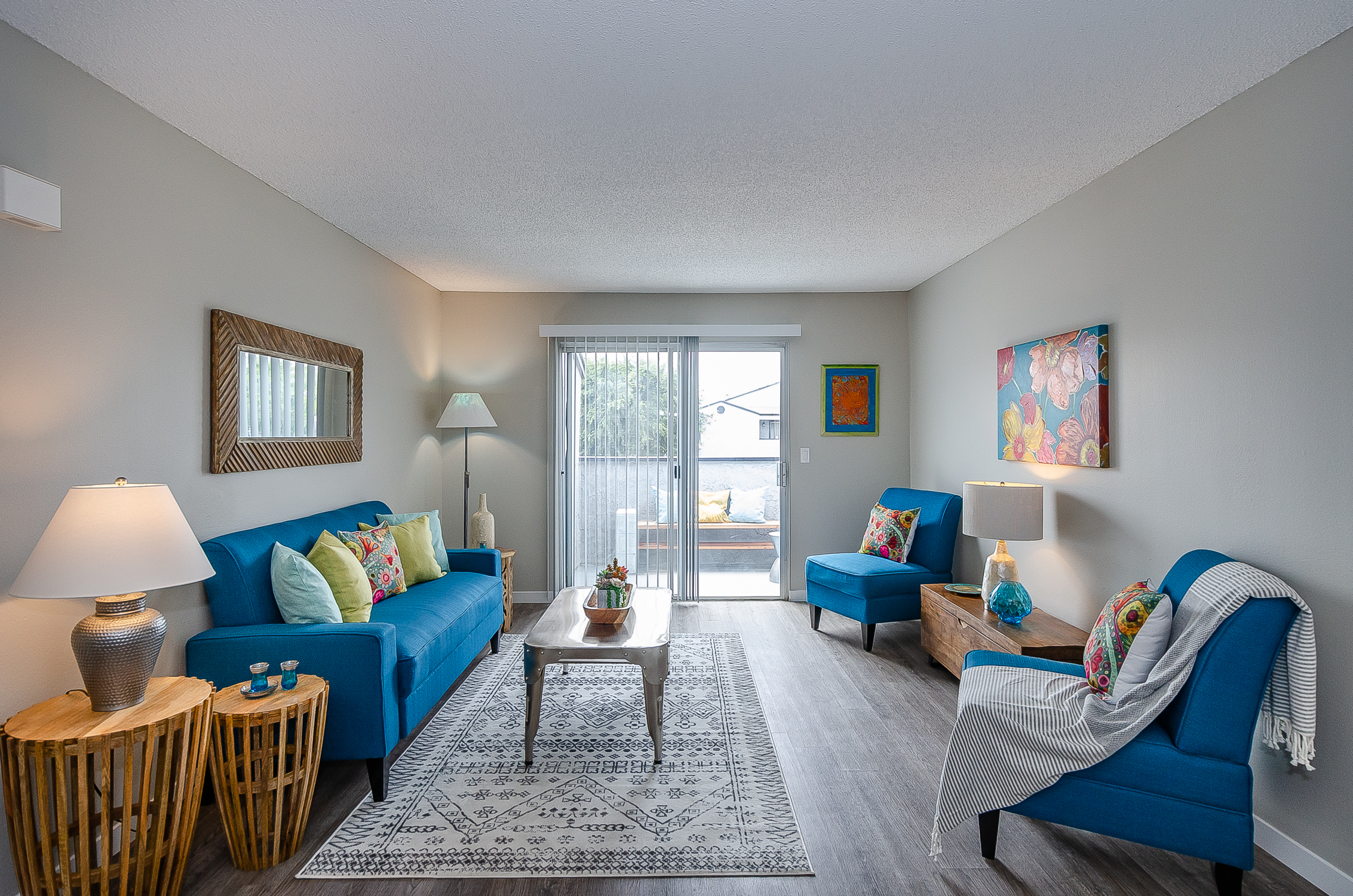 living room has wood-type plank flooring, a sliding door to the patio, and 2 walls for furniture