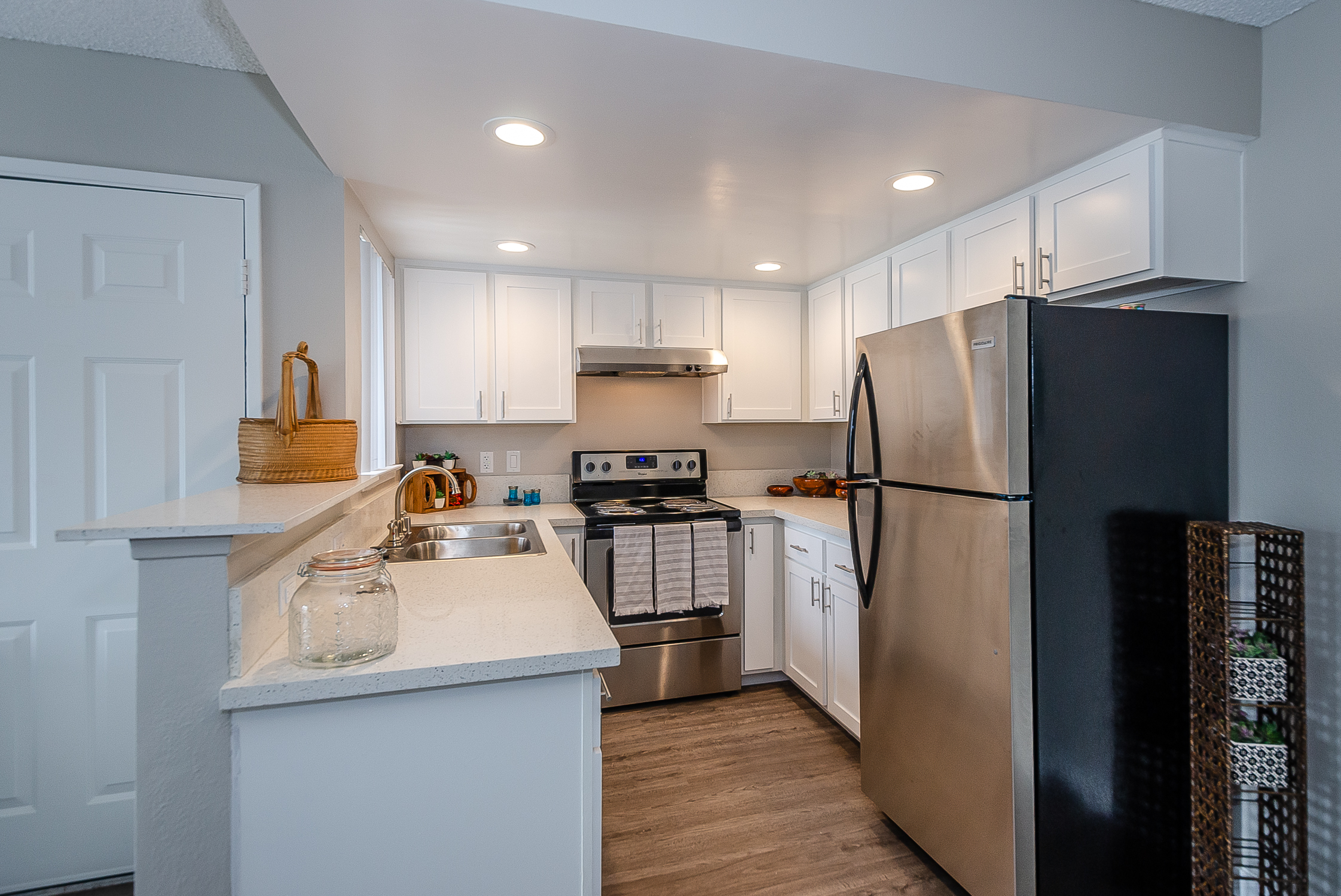 kitchen with recessed lights, dishwasher, tall bar counter, stainless appliances and wood-look floor