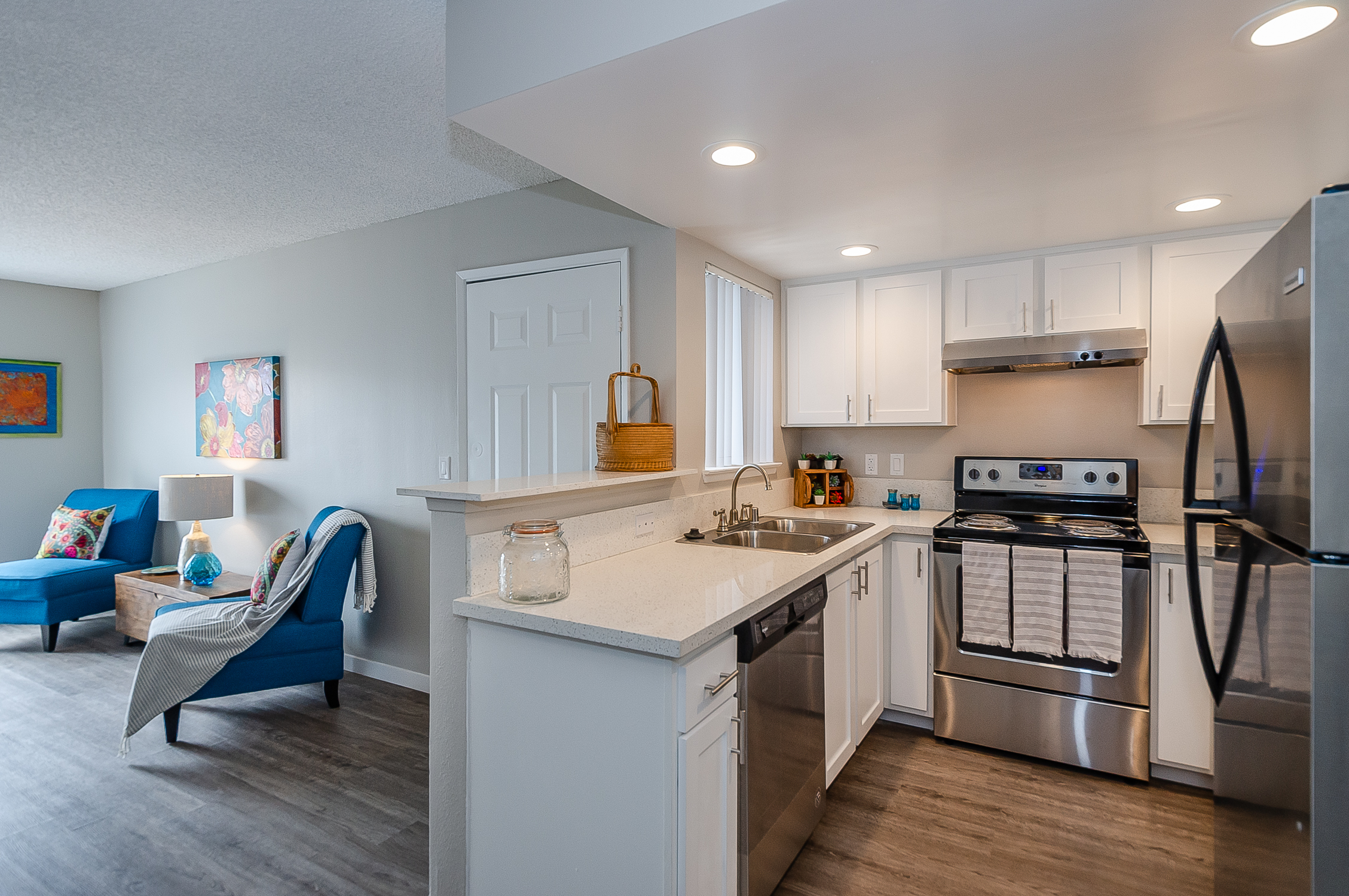 kitchen with recessed lights, dishwasher and stainless appliances opens to dining and living areas