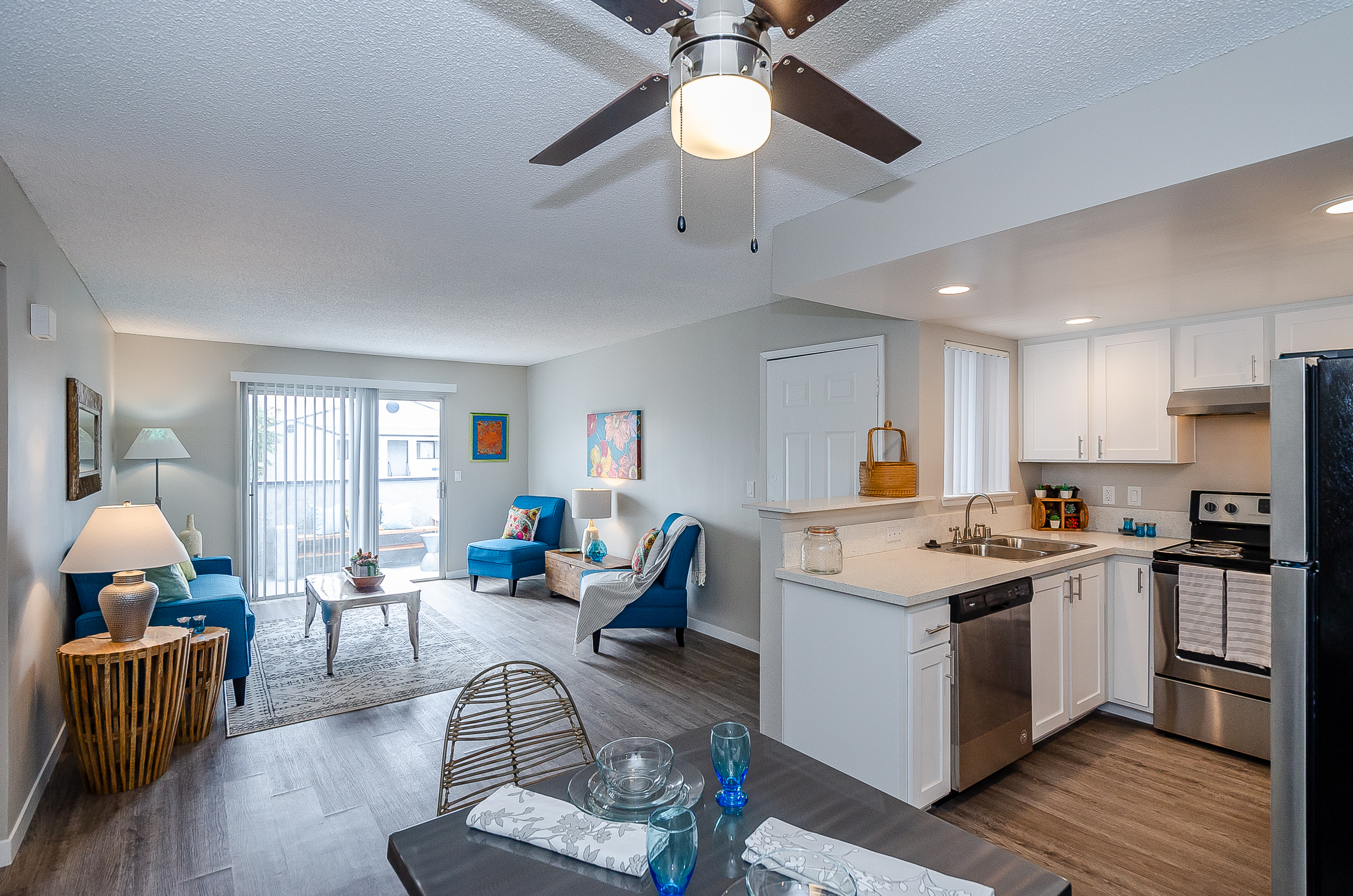 kitchen opens to dining and tall counter opens to living room, with wood-look flooring throughout