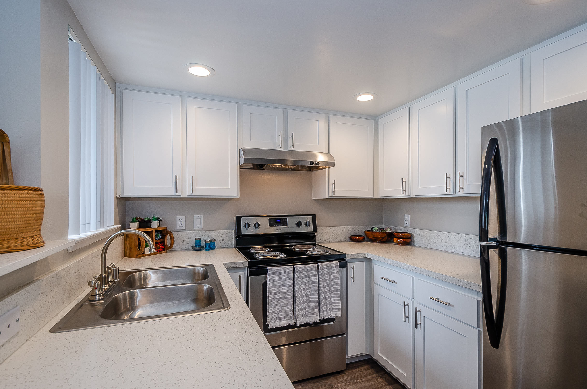 kitchen with stainless steel appliances, double sink, window, painted cabinets with sleek hardware