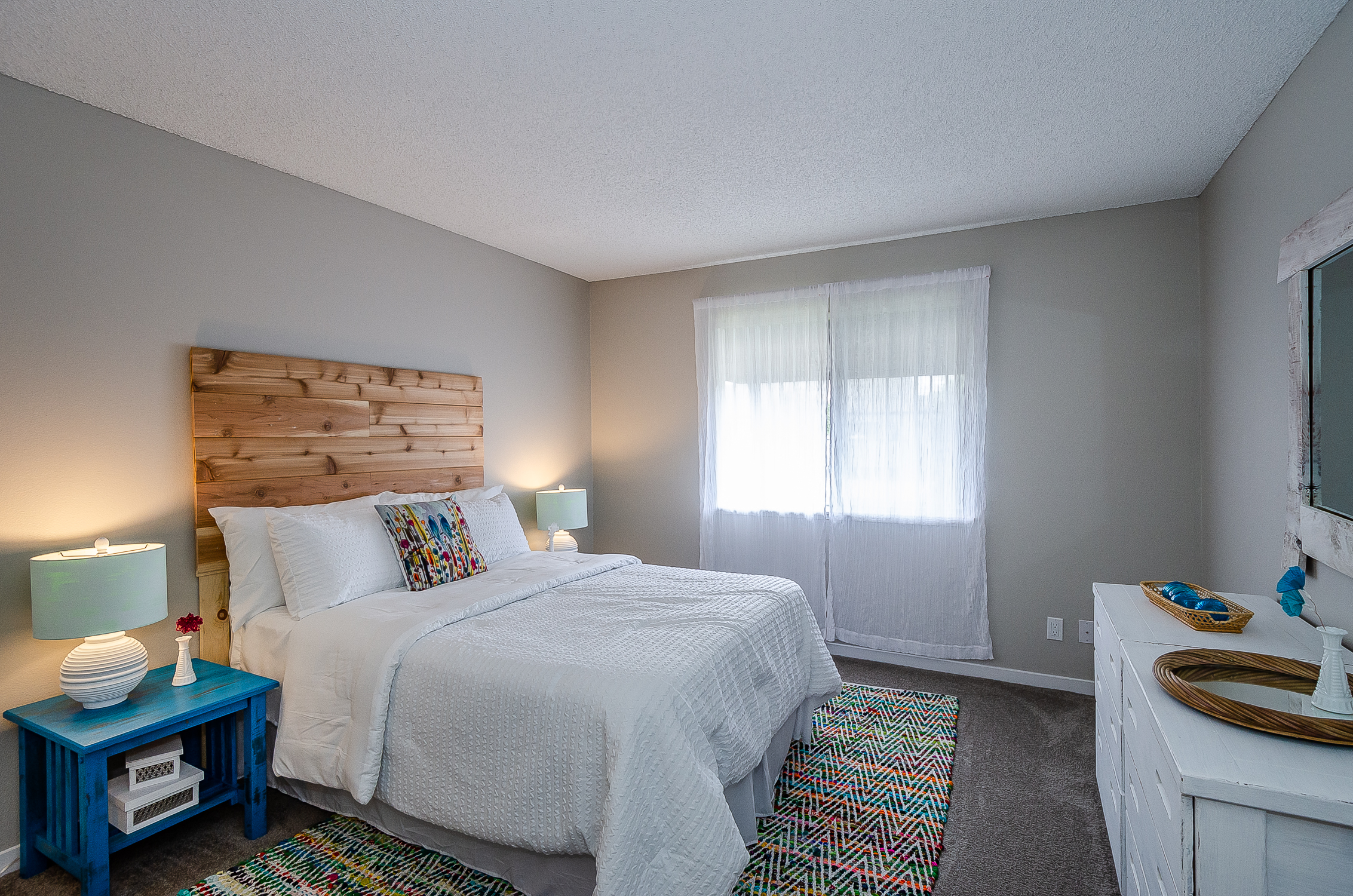 carpeted bedroom with window shows plenty of room for a large bed, a wide dresser, and 2 nightstands