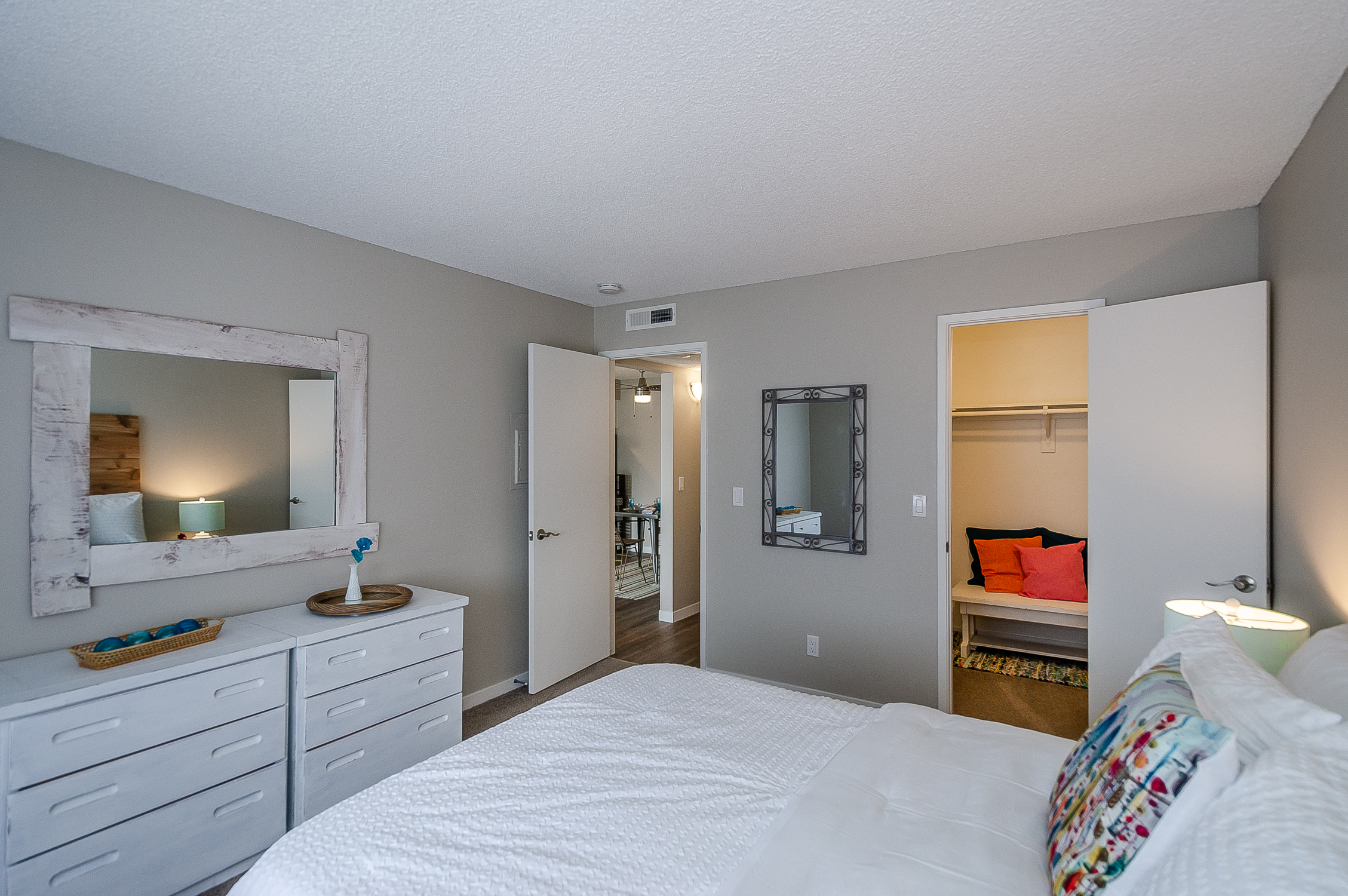 bedroom shows a deep closet, carpet flooring, and view into the hallway that has wood flooring