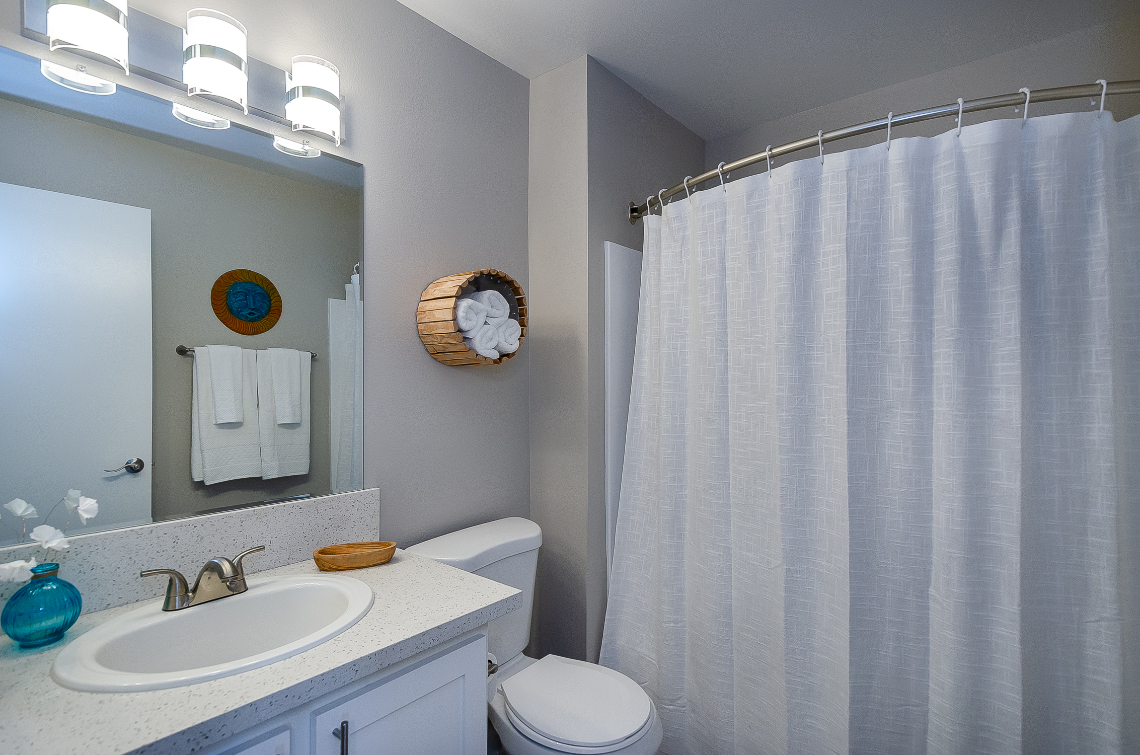 clean modern bathroom with curved shower curtain rod, vanity lights, and double cabinet under sink