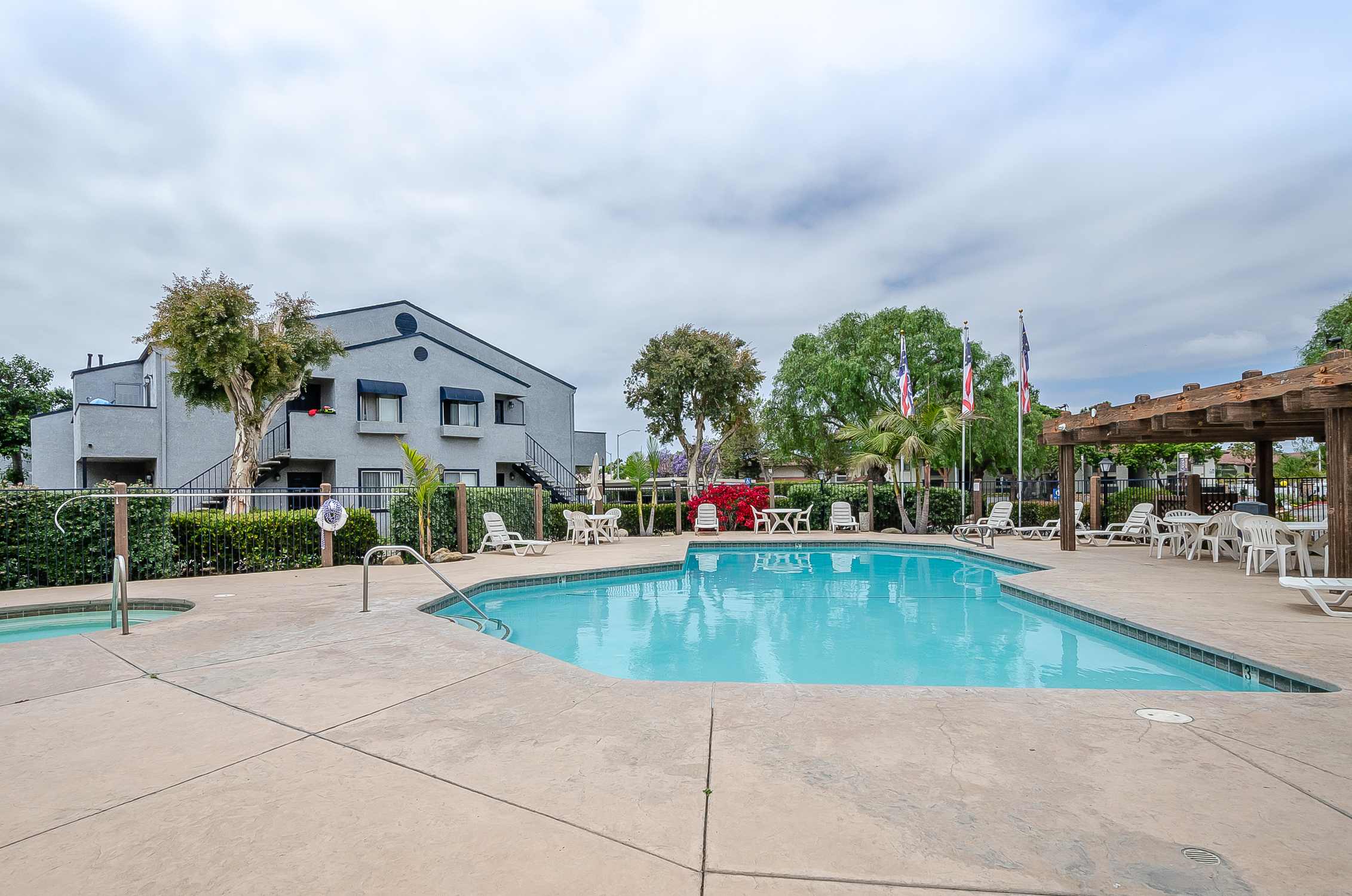 fenced pool, hot tub and patio in apartment complex with lounges, tables and chairs, and wood awning